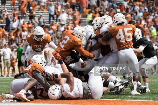 Malik Jefferson of the Texas Longhorns and Poona Ford stop Toneil Carter on the goal line during the final play of the OrangeWhite Spring Game at...