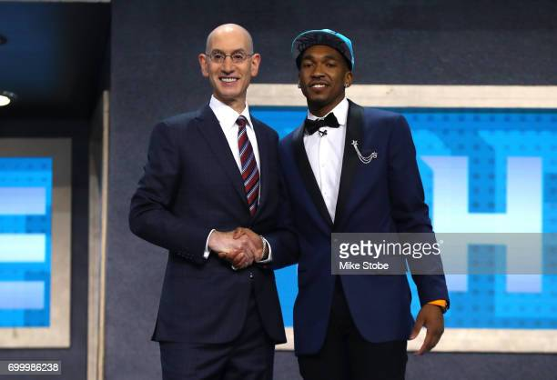 Malik Monk walks on stage with NBA commissioner Adam Silver after being drafted eleventh overall by the Charlotte Hornets during the first round of...