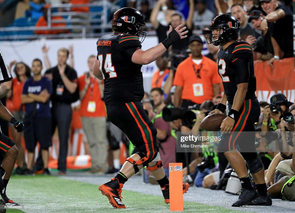 Malik Rosier #12 and Tyler Gauthier #74 of the Miami Hurricanes celebrate a touchdown during a game against the Virginia Tech Hokies at Hard Rock Stadium on November 4, 2017 in Miami Gardens, Florida.