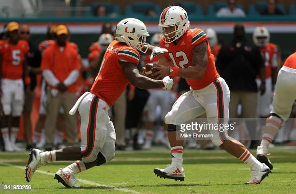 Malik Rosier hands off to Mark Walton of the Miami Hurricanes during a game at Hard Rock Stadium on September 2 2017 in Miami Gardens Florida