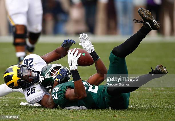 Malik Smith of the Michigan State Spartans makes a fourth quarter catch next to Jourdan Lewis of the Michigan Wolverines at Spartan Stadium on...