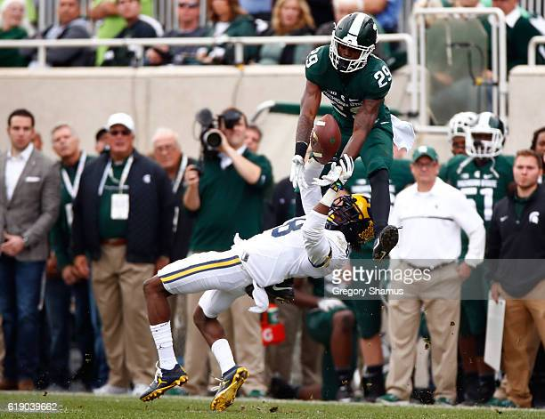 Malik Smith of the Michigan State Spartans tries to pull down a fourth quarter catch over Channing Stribling of the Michigan Wolverines at Spartan...