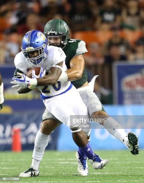Malike Roberson of the San Jose State Spartans is tacked by Russell Williams Jr of the Hawaii Rainbow Warriors during the second quarter of their...
