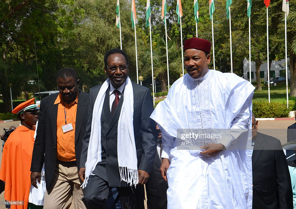 Mali's interim government President Dioncounda Traore (C) walks alongside Niger's President Mahamadou Issoufou (R) at the presidential palace in Niamey, Niger, on December 2, 2012. Malian army colonel Alaji Ag Gamou, a Tuareg, who has been stationed for several months in Niger after Islamist militants took control of northern Mali, escaped an assassination attempt on December 2 in Niamey. Burkina Faso's President and Malian crisis mediator Blaise Compaore will present to Malian government representatives a 'negotiations agenda' with the Ansar Dine and National Movement for the Liberation of Azawad (MNLA) armed groups on December 3.