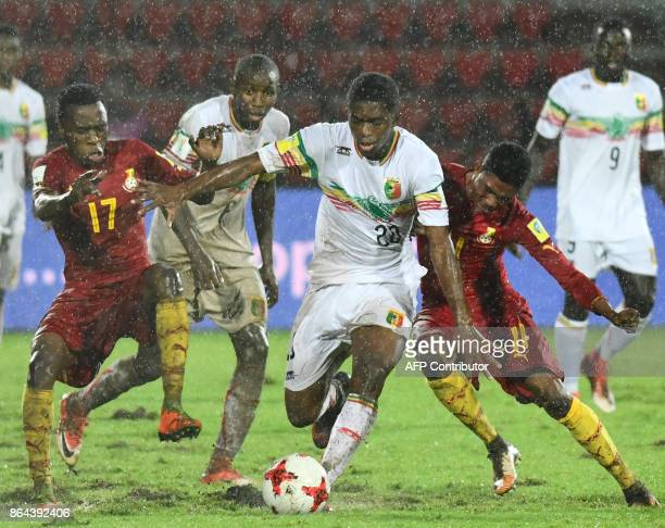 Malis midfielder Cheick Oumar Doucoure vies for the ball with Ghanas defender Rashid Alhassan and forward Aminu Mohammed during the FIFA U17 World...