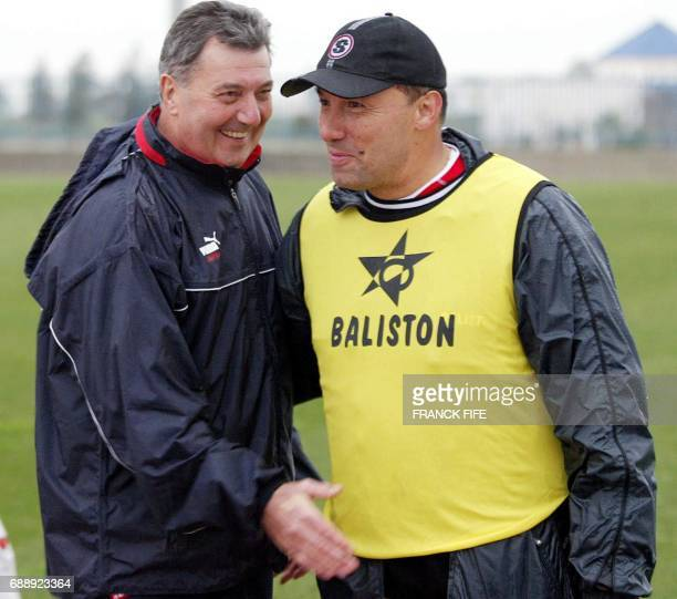 Mali's national team coach French Henry Stambouli talks to compatriot Tunisia's coach Roger Lemerre after a training session 23 January 2004 in Tunis...