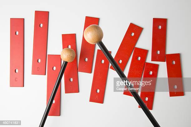 Mallets preparing to play bars from a xylophone missing its base