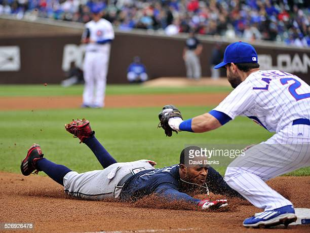 Mallex Smith of the Atlanta Braves is about to be tagged out at third base as he tries for a triple by Tommy La Stella of the Chicago Cubs on May 1...