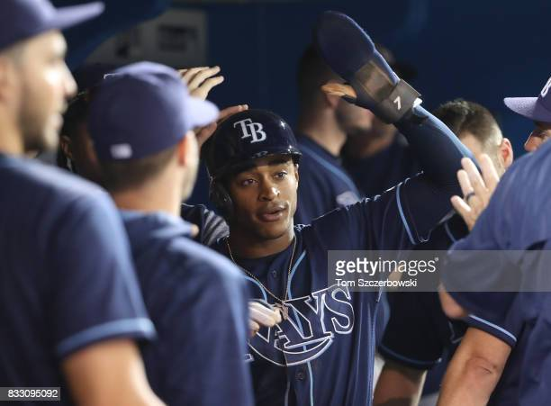 Mallex Smith of the Tampa Bay Rays is congratulated by teammates in the dugout after scoring a run on a basesloaded walk in the seventh inning during...