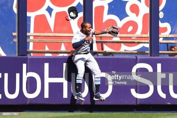 Mallex Smith of the Tampa Bay Rays slams into the outfield wall after failing to make a catch during the game against the New York Yankees at Yankee...