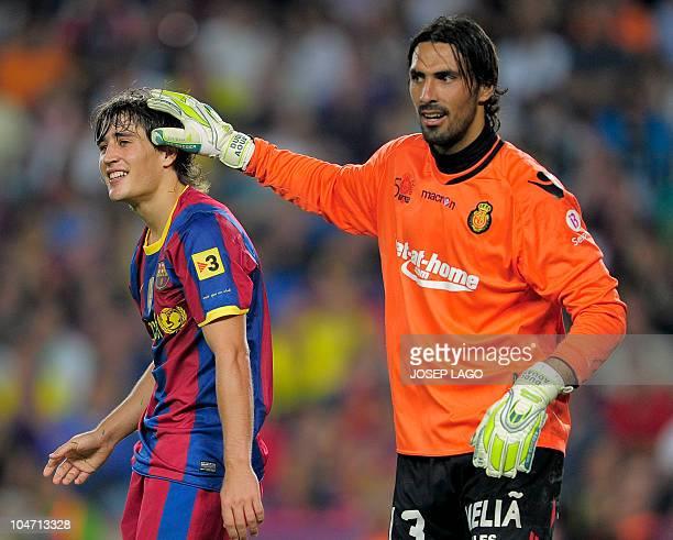 Mallorca's Argentinian goalkeeper Israeli goalkeeper Dudu Aouate touches the head of Barcelona's forward Bojan Krkic during their first league...