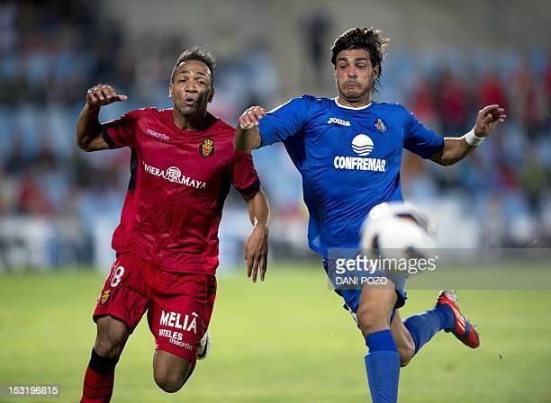 Mallorca's forward Emilio Nsue vies for the ball with Getafe's defender Miguel Torres during the Spanish league football match Getafe vs Mallorca at...