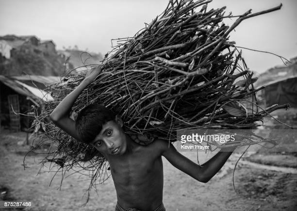 COX'S BAZAR BANGLADESH OCTOBER 23 A malnourished Rohingya refugee boy carries firewood he scavenged on October 23 2017 at the Balukhali refugee camp...