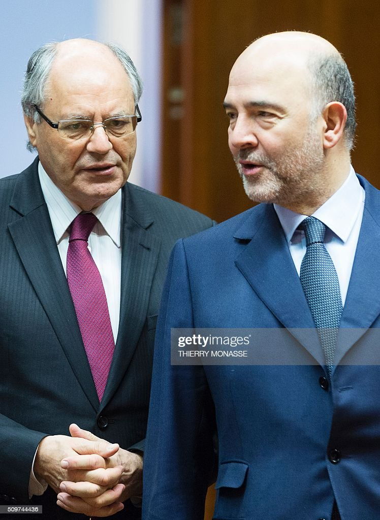 Malta's Finance Minister Edward Scicluna (L) and European Commissioner for Economic and Financial Affairs, Taxation and Customs Pierre Moscovici attend the European Union Eco-Finance Council meeting at the EU Council building in Brussels on February 12, 2016. AFP PHOTO / THIERRY MONASSE / AFP / THIERRY MONASSE