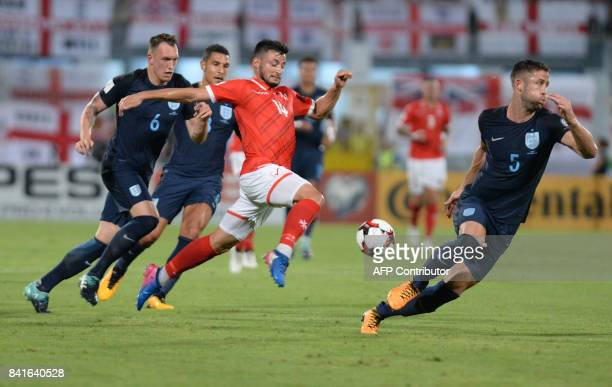 Malta's Jean Paul Farrugia makes his way between England's Phil Jones and England's Gary Cahill during the FIFA 2018 World Cup Qualifying Group F...