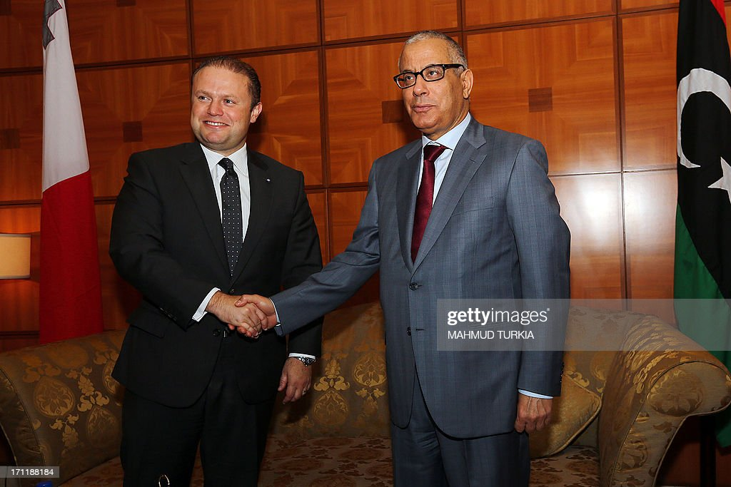 Malta's Prime Minister Joseph Muscat (L) shakes hands with his Libyan counterpart Ali Zeidan upon his arrival at Tripoli international airport for an official visit on June 23, 2013.
