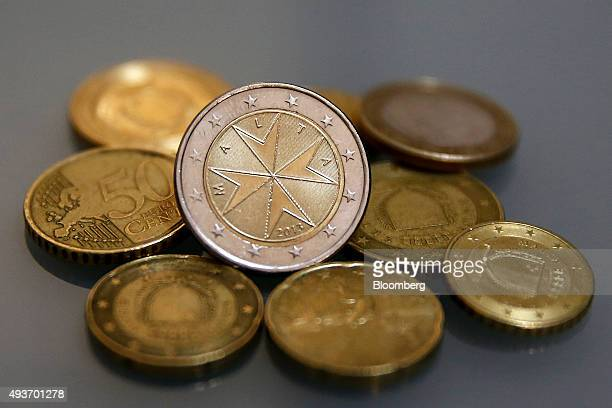 A Maltese cross sits on a two euro coin with other euro cent coins in this arranged photograph in Valletta Malta on Wednesday Oct 21 2015 ECB...