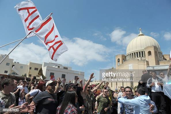 Maltese hunters wave IVA flags as they gather to celebrate the result of the referendum on hunting on April 12 2015 in Qormi Malta has voted in a...
