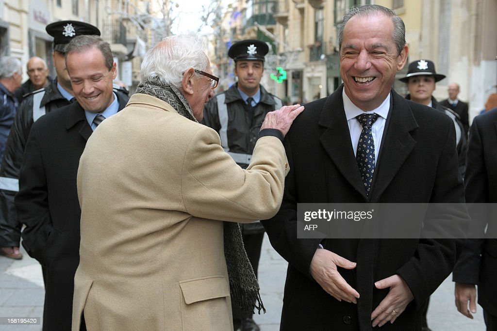 Maltese Prime Minister Lawrence Gonzi (R) is greeted by a supporter, as he leaves after a meeting with the Maltese President, the day after the centre-left government lost its majority in parliament on December 11, 2012 in Valetta. Gonzi said the same day the parliament would be dissolved on January 7 ahead of the election following an agreement by both main political parties not to begin the election campaign during the Christmas season.
