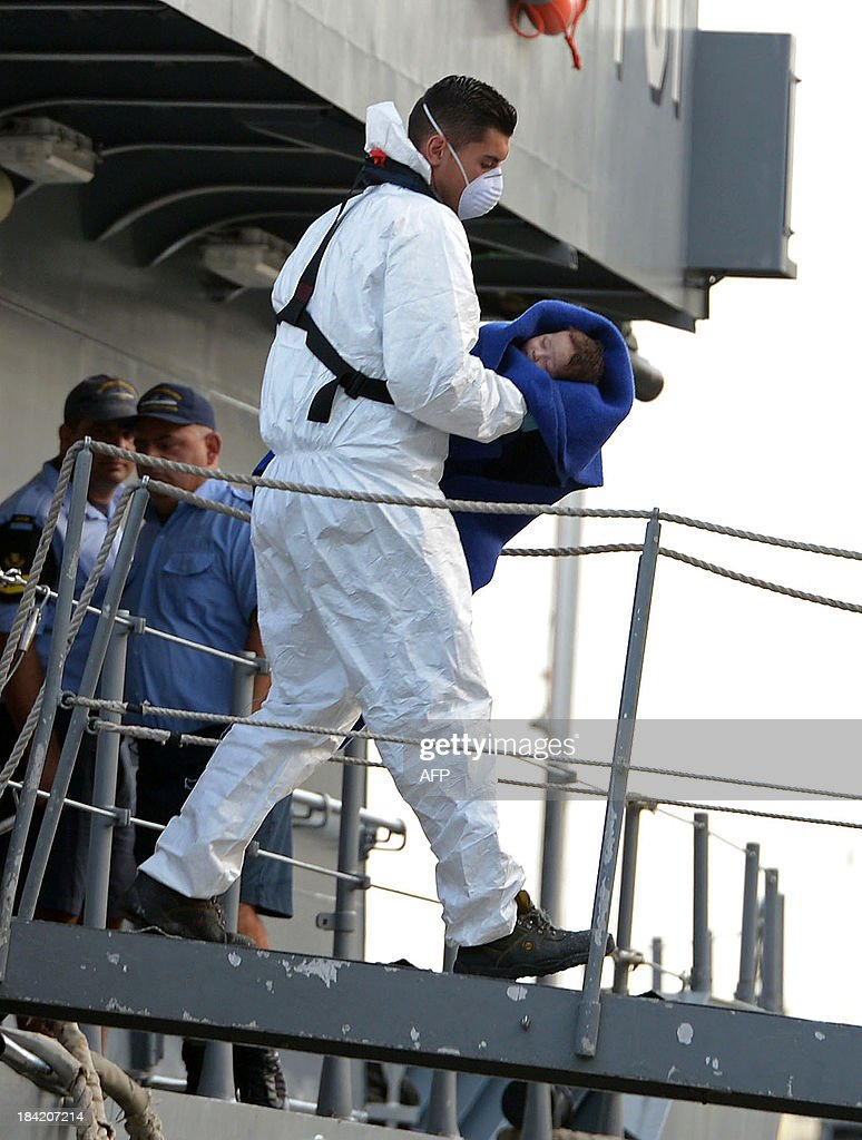 A Maltese rescue worker carries a baby rescued by the Armed forces of Malta at Hay Wharf in Valletta on October 12, 2013. More than 140 survivors, plucked from the sea after their overloaded boat sank in the latest deadly migrant tragedy to hit the Mediterranean, arrived in Malta. The sinking killed more than 30, most of them women and children, when the boat packed with people desperate to reach European shores went down off Malta near the Italian island of Lampedusa, according to officials. AFP PHOTO/MATTHEW MIRABELLI
