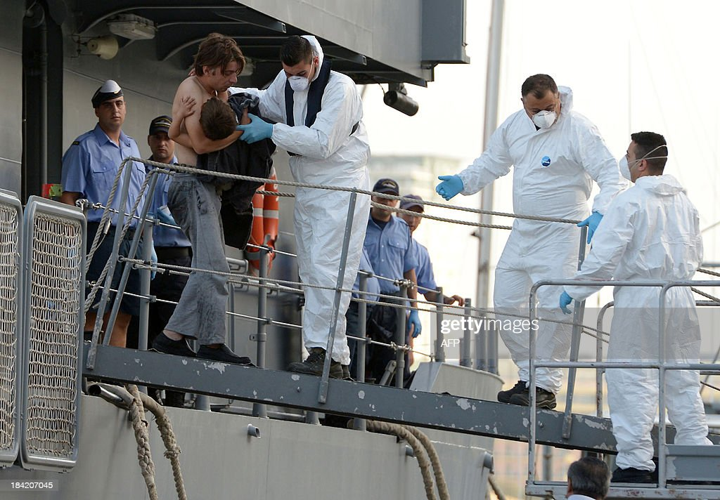 Maltese rescue workers assist a migrant carrying a child upon arrival at Hay Wharf in Valletta aboard a patrol boat of the Armed forces of Malta on October 12, 2013. More than 140 survivors, plucked from the sea after their overloaded boat sank in the latest deadly migrant tragedy to hit the Mediterranean, arrived in Malta. The sinking killed more than 30, most of them women and children, when the boat packed with people desperate to reach European shores went down off Malta near the Italian island of Lampedusa, according to officials.