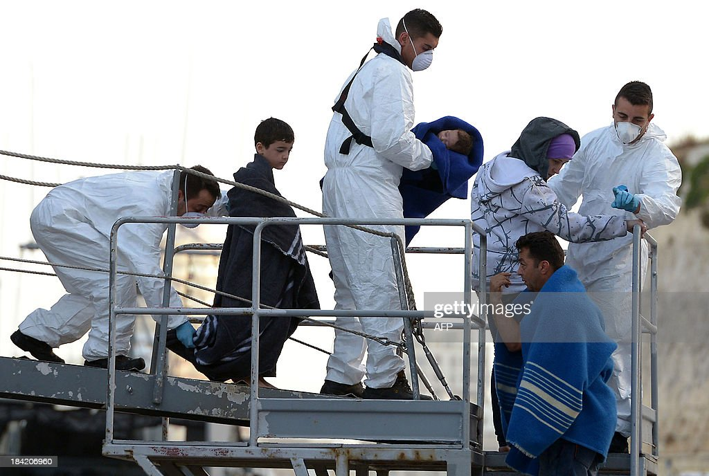 Maltese rescue workers escort a migrant family upon arrival at Hay Wharf in Valletta after being rescued by a patrol boat of the Armed forces of Malta on October 12, 2013, a day after a boat carrying migrants sank. More than 140 survivors, plucked from the sea after their overloaded boat sank in the latest deadly migrant tragedy to hit the Mediterranean, arrived in Malta. The sinking killed more than 30, most of them women and children, when the boat packed with people desperate to reach European shores went down off Malta near the Italian island of Lampedusa, according to officials.