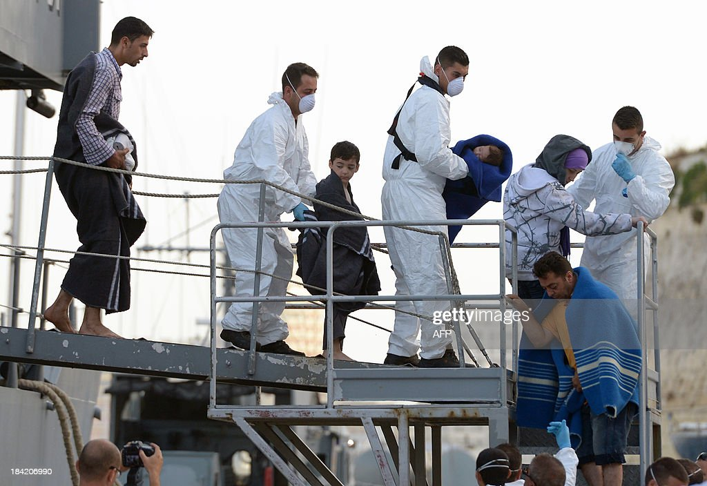 Maltese rescue workers escort migrants upon arrival at Hay Wharf in Valletta after being rescued by a patrol boat of the Armed forces of Malta on October 12, 2013, a day after their boat sank. More than 140 survivors, plucked from the sea after their overloaded boat sank in the latest deadly migrant tragedy to hit the Mediterranean, arrived in Malta. The sinking killed more than 30, most of them women and children, when the boat packed with people desperate to reach European shores went down off Malta near the Italian island of Lampedusa, according to officials.