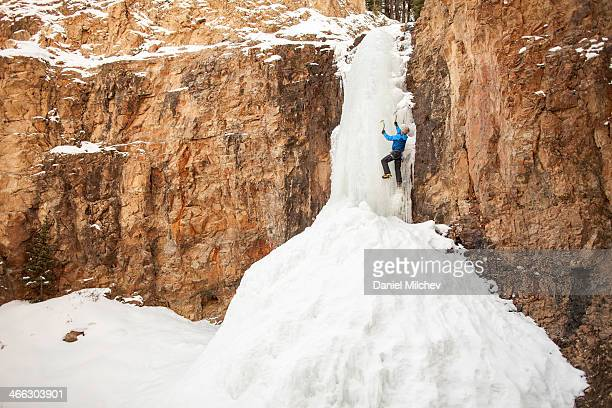Mam climbing a frozen waterfall in the wildernerss