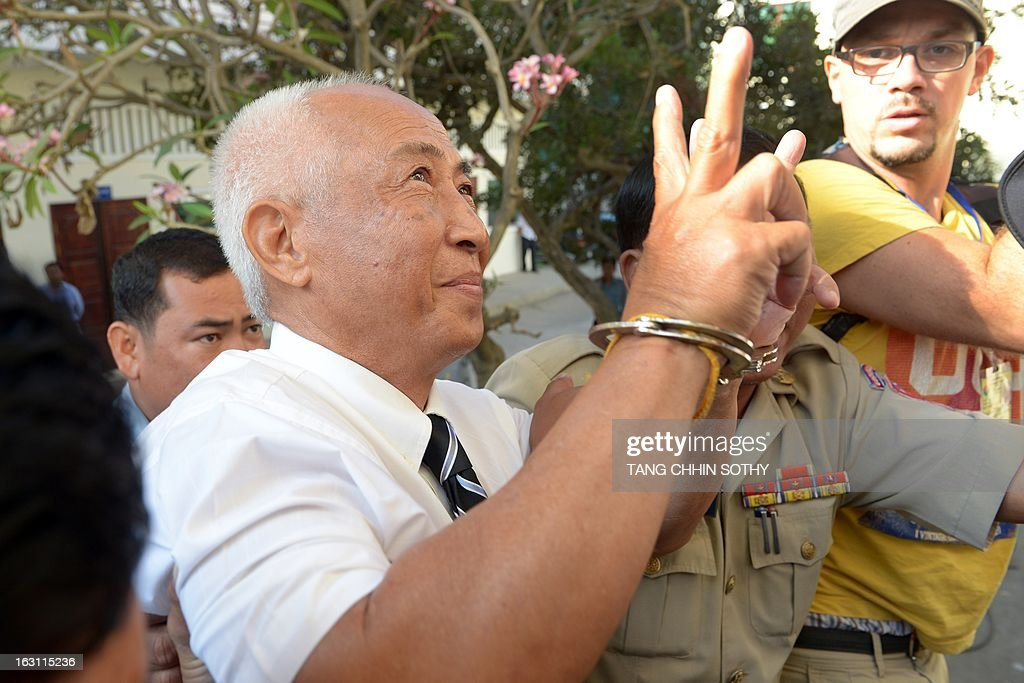 Mam Sonando (C), owner of the independent Beehive radio station, gestures upon his arrival as prison guards escort him to the Appeal court in Phnom Penh on March 5, 2013. A prominent critic of Cambodia's government, sentenced to 20 years in prison for an alleged secessionist plot, on March 5, pleaded not guilty during his appeal hearing.