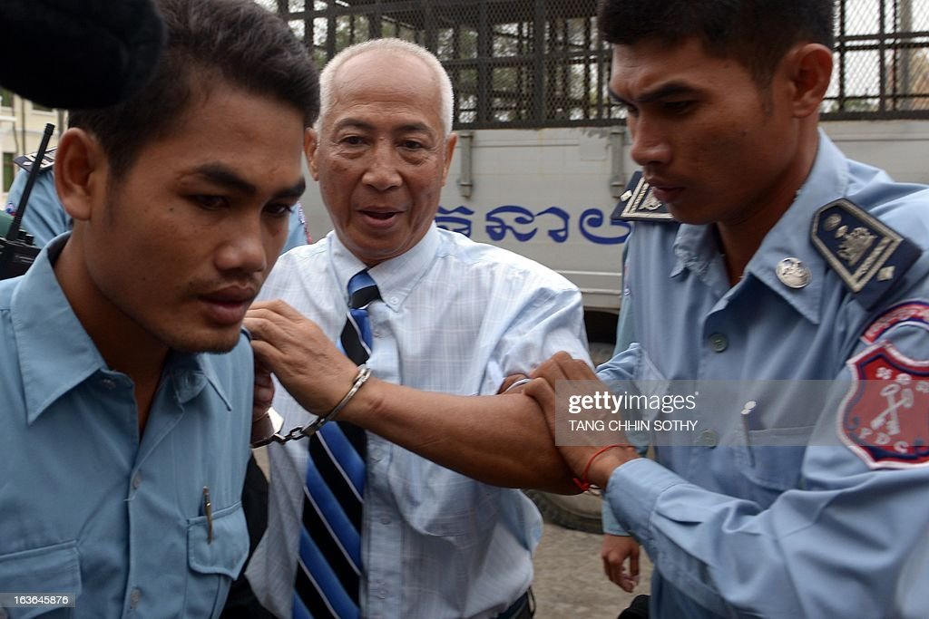 Mam Sonando (C), owner of the independent Beehive radio station, is escorted by prison guards to the Appeal Court in Phnom Penh on March 14, 2013. The Cambodian Appeal Court on March 14 cleared the prominent government critic Sonando, who has dual Cambodian-French citizenship, of a secessionist plot, slashing his 20-year jail term and ordering his release from prison over the next few days. AFP PHOTO / TANG CHHIN SOTHY