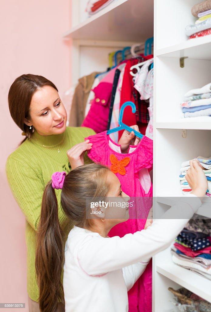 mam ensinando Menina escolha Roupas : Foto de stock