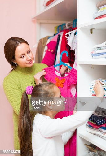 mam teaching girl to choose clothes : Stock Photo