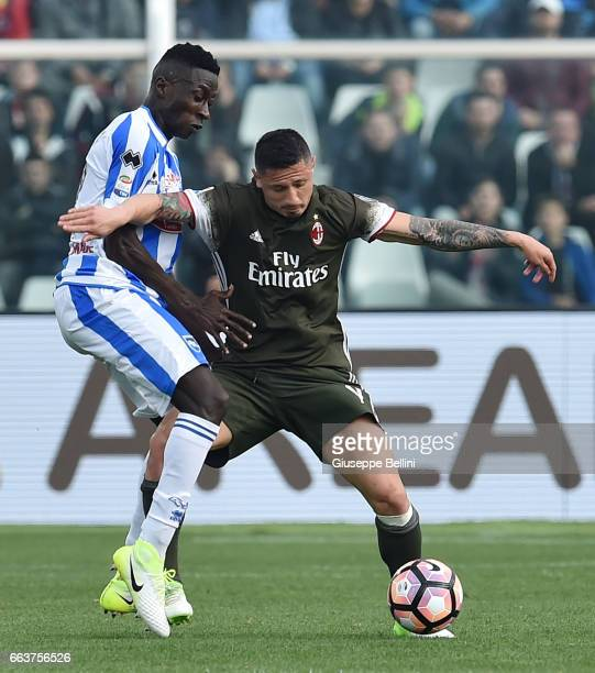 Mamadou Coulibaly of Pescara Calcio and Gianluca Lapadula of AC Milan in action during the Serie A match between Pescara Calcio and AC Milan at...