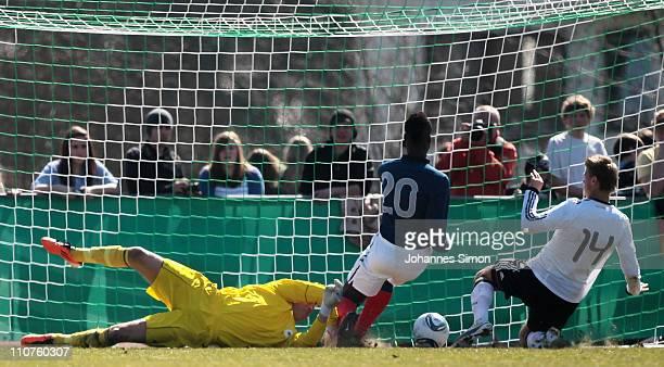 Mamadou Doucoure of France scores his team's first goal against German goalkeeper Loris Karius and Florian Hartherz during the U18 international...