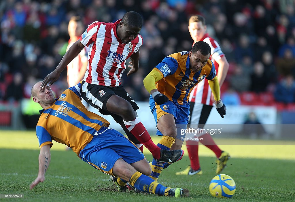 Mamadou Fofana of Lincoln City is tackled by Adam Murray of Mansfield Town as Matt Green looks on during the FA Cup with Budweiser Second Round match at Sincil Bank Stadium on December 1, 2012 in Lincoln, England.