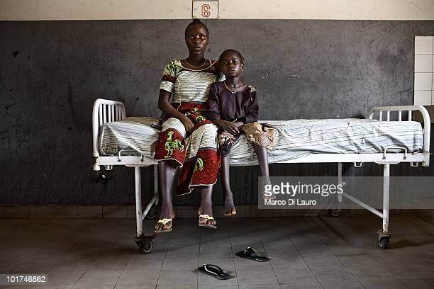 Mamaista Soumah 15yearsold seats with her sister Fatoumata Soumah who has malaria symtoms on a bed during British Actor and UNICEF Ambassador James...