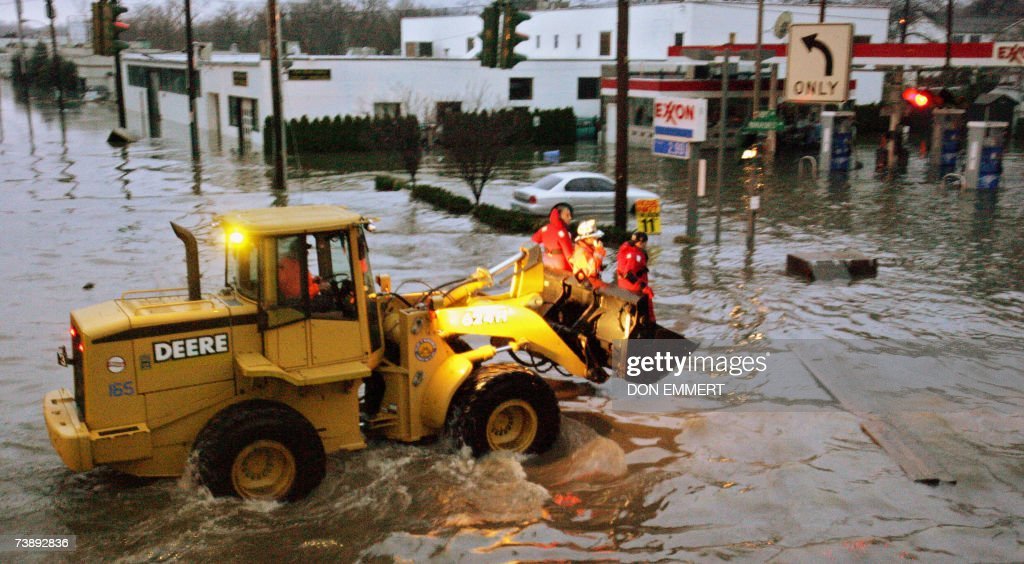 Emergency workers ride a front end loader through floodwater on Mamaroneck Ave 15 April 2007 in Mamaroneck New York Flood waters from heavy rainfall...