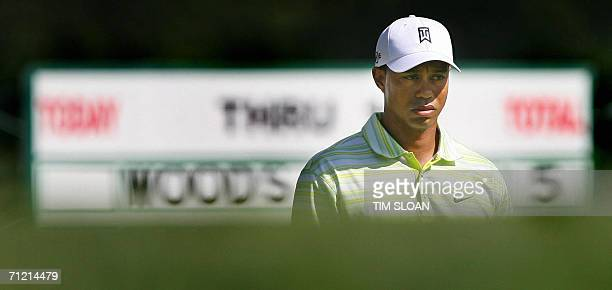Tiger Woods of the US stands before a sign board displaying his 5 over par showing as of the 12th green during the opening round of the 106th US Open...