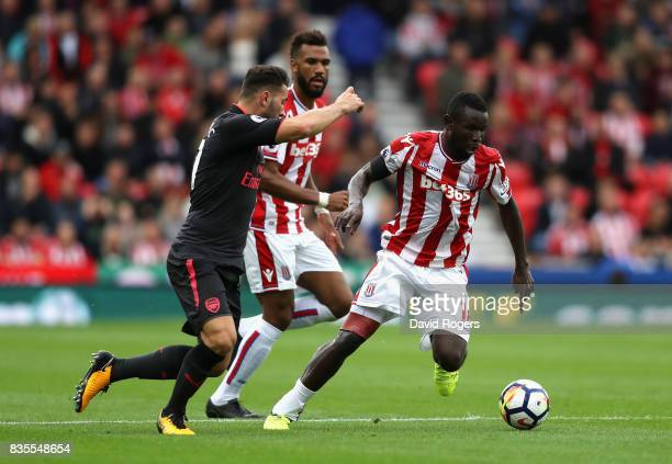 Mame Biram Diouf of Stoke City attempts to take the ball past Sead Kolasinac of Arsenal during the Premier League match between Stoke City and...