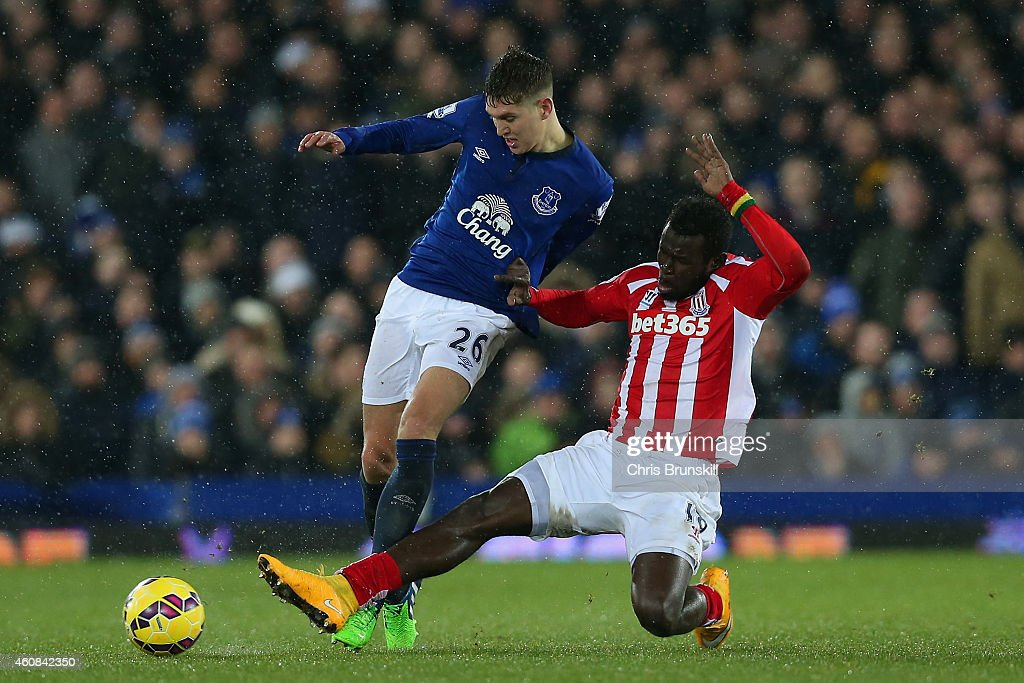 Mame Biram Diouf of Stoke City tackles John Stones of Everton during the Barclays Premier League match between Everton and Stoke City at Goodison Park on December 26, 2014 in Liverpool, England.