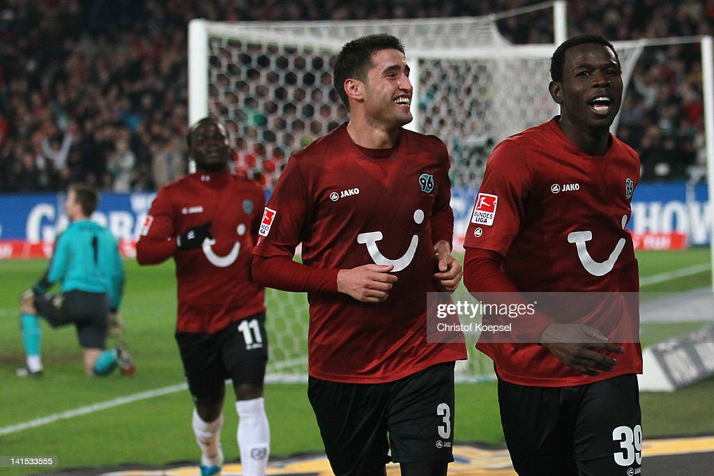 Mame Diouf of Hannover (R) celebrates the forth goal with Karim Haggui (C) and Didier Ya Konan (L) of Hannover during the Bundesliga match between Hanover 96 and 1. FC Koeln at AWD Arena on March 18, 2012 in Hannover, Germany.