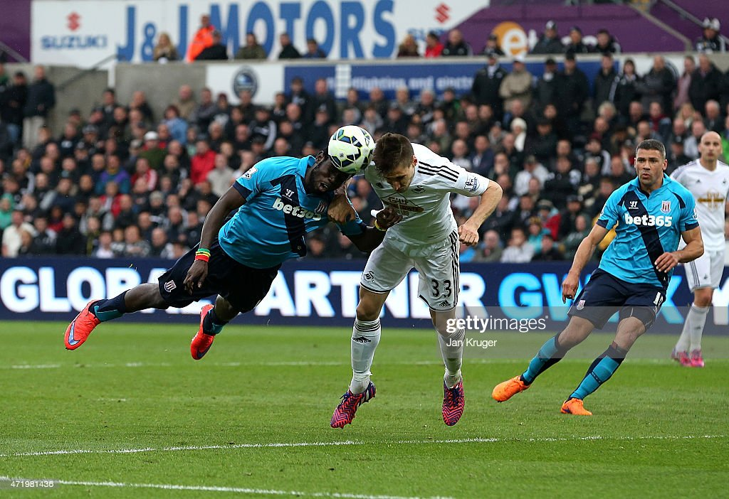 Mame Diouf of Stoke City heads the ball toward goal under pressure from Federico Fernandez of Swansea City during the Barclays Premier League match between Swansea City and Stoke City at Liberty Stadium on May 2, 2015 in Swansea, Wales.