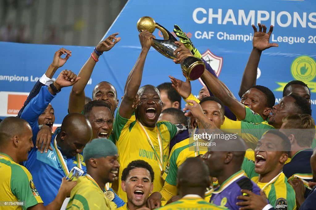 Mamelodi Sundowns' players celebrate with the trophy after winning the CAF Champions League football competition following the final match against Egypt's Zamalek on October 23, 2016 at the Borg el-Arab Stadium near Alexandria. / AFP / STRINGER