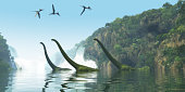 Two Mamenchisaurus dinosaur adults escort a youngster across a river as Pterodactylus birds search for fish prey.