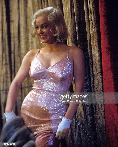 Mamie Van Doren US actress and singer wearing a light pink sequinned thinstrap dress white gloves and diamond earrings circa 1960
