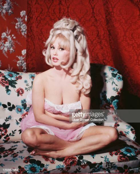 Mamie Van Doren US actress and singer wearing a pink strapless nightdress with white lace trim which has fallen down to reveal her cleavage as she...