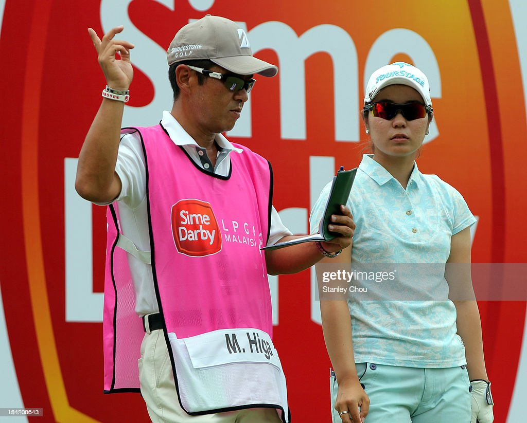 Mamiko Higa of Japan and her caddie on the 9th hole during day three of the Sime Darby LPGA at Kuala Lumpur Golf Country Club on October 12 2013 in...