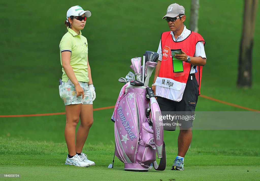Mamiko Higa of Japan and her caddie waits on the 4th hole during day two of the Sime Darby LPGA Malaysia at Kuala Lumpur Golf Country Club on October...