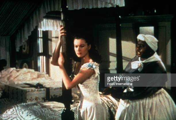 Mammy played by American actress Hattie McDaniel tightens the corset of Scarlett O'Hara played by English actress Vivien Leigh in a scene from 'Gone...