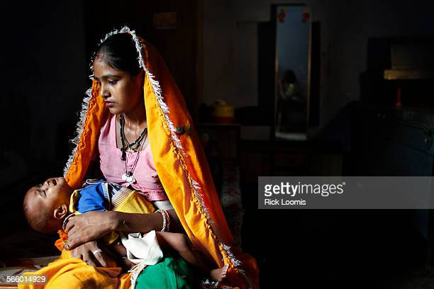 Mamta still a child herself being born on January 1 holds her youngest child in the room that she and her husband share with her extended family in...